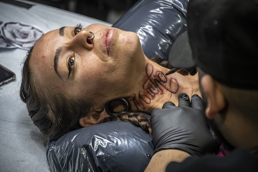 "Tattoo artist David Chavera, of Local Boy Tattoo in San Antonio, Texas, preps a ""Much Love"" design in Spanish on the neck of Roxanne Reche, of Willow Creek. - PHOTO BY MARK LARSON"