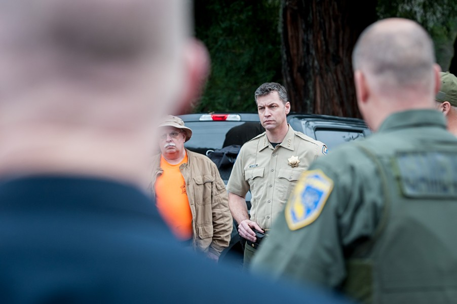 Sheriff William Honsal looks on during a debriefing with search teams returning from the field. - MARK MCKENNA
