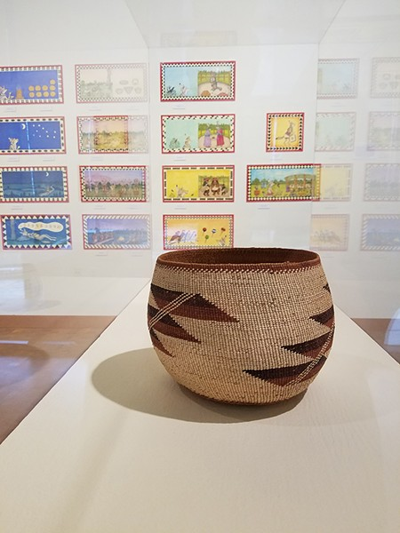 An early 20th-century Karuk basket in front of paintings by Lyn Risling. - PHOTO BY GABRIELLE GOPINATH