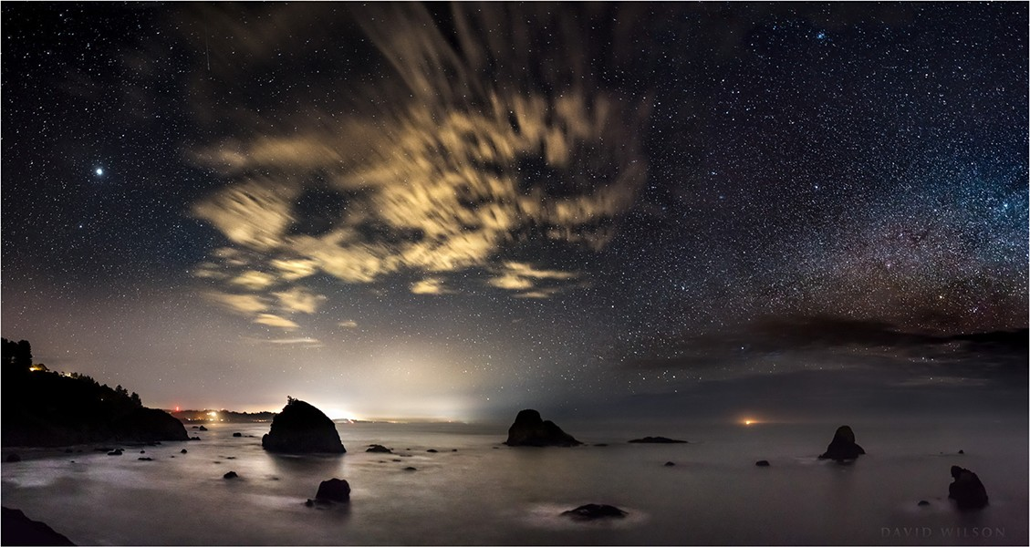 The rugged northern California coast is battered by a constant barrage of waves, their motion smoothed out in this 25-second exposure. Puffy clouds blowing by overhead were changed to streaks in the camera by their motion. Only the stars and rocks appeared to be still. - DAVID WILSON