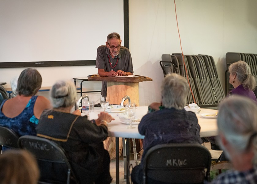 Brian Tripp reads poems before picking up his square drum. - PHOTO BY ZACH LATHOURIS