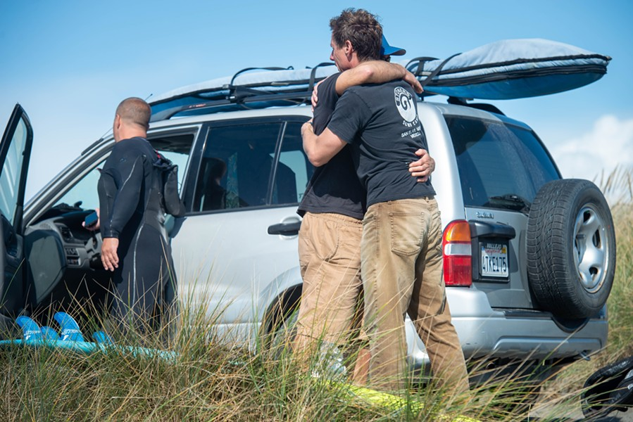 Jim Merryfield, one of four regular surfers at the North Jetty who rendered aid to Hargrave, hugs a friend on the dunes shortly after returning to shore. All four of the surfers described Hargrave as a great guy and experienced surfer. - MARK MCKENNA