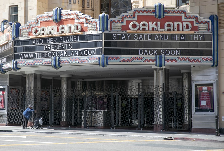 A woman pushes a cart past the shuttered Fox Theater in downtown Oakland on March 25, 2020. - ANNE WERNIKOFF FOR CALMATTERS