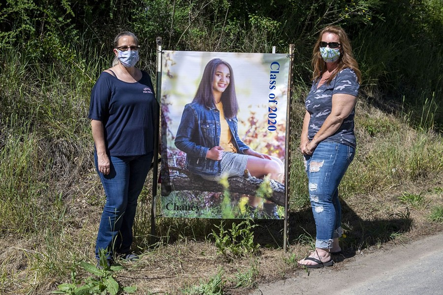 Two of the organizers of the special event, Lori Ruiz, left, and Michelle Bushnell, stand with another of the senior portraits. - MARK MCKENNA