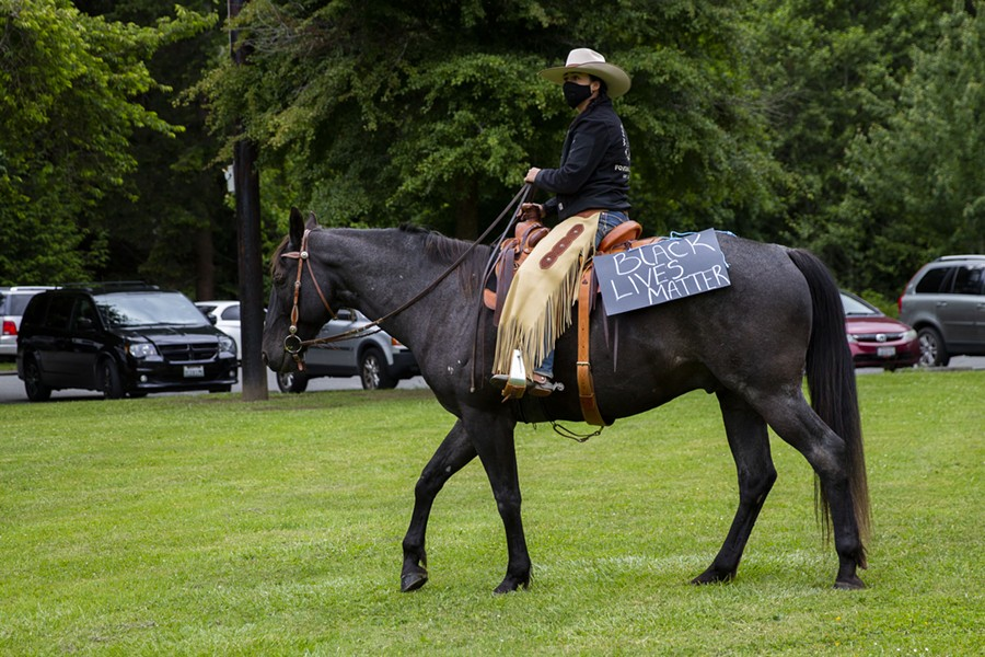 Wild Souls Ranch Executive Director Savanah McCarthy rides with a Black Lives Matter sign on her horse at Rohner Park in Fortuna while demonstrators gather to protest police brutality and racism on June 5. - THOMAS LAL