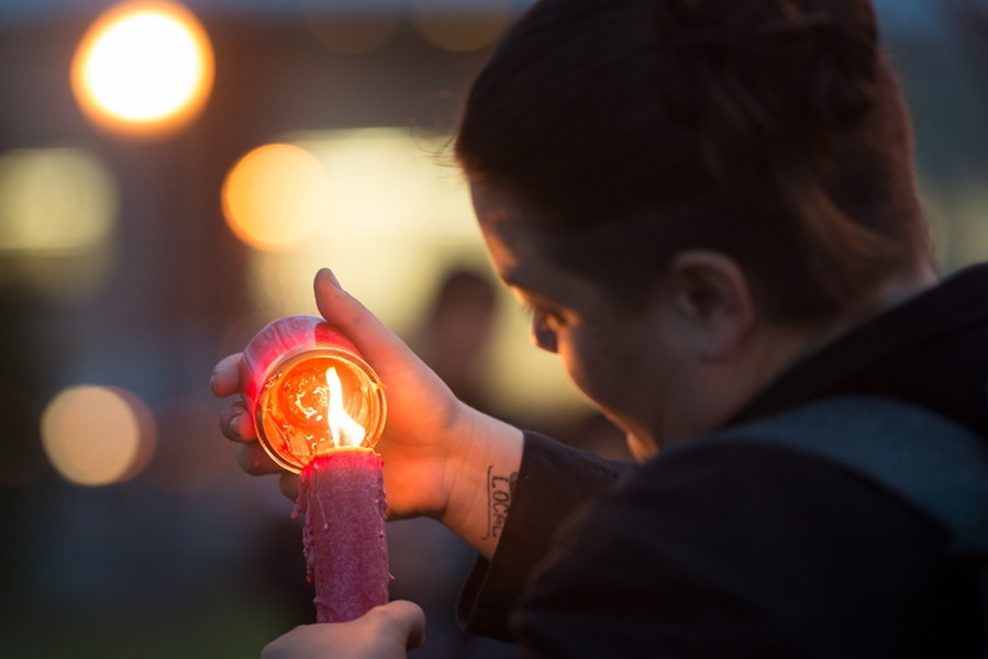 Molly Conso lights a candle at the end of the vigil. - MARK MCKENNA