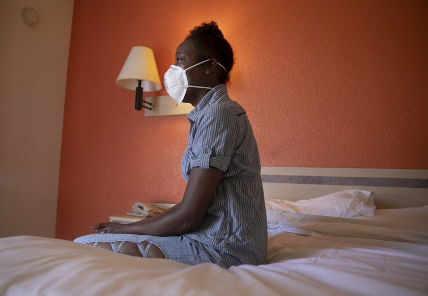 Jamie Burson sits on the bed of her motel room in Farfield on August 4, 2020. Burson, who has been homeless since being evicted in April, says she spends all of her time in her room with the curtains closed. - ANNE WERNIKOFF FOR CALMATTERS