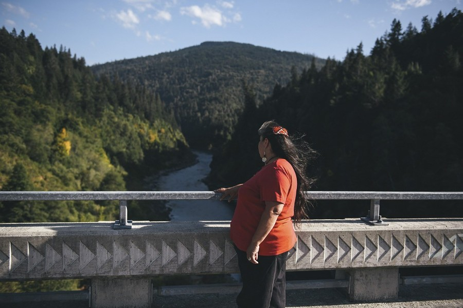 Portrait of Celinda Gonzales in Weitchpec on Sep. 17. Gonzales looks off over the Klamath River toward a large rock where her thrill-seeking son Paul Moreno used to jump off into the water. He later died by suicide. - ALEXANDRA HOOTNICK FOR CALMATTERS
