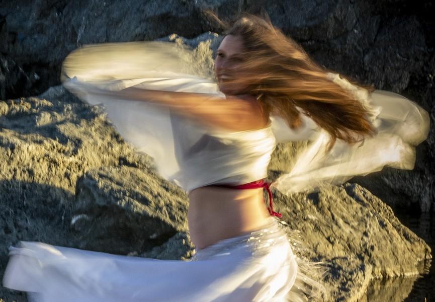 "Isadora Sharon spun around while rehearsing ""Veil/Re-Veil"" on Moonstone Beach before sunset Saturday. - PHOTO BY MARK LARSON"