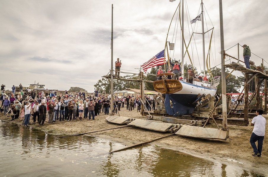 After an opening ceremony, a large crowd gathered on the edge of Humboldt Bay to watch the Golden Rule's launching on Saturday, June 20 at the Zerlang & Zerlang boat yard on the Samoa peninsula. The vessel was then towed by tug to the HSU aquatic center on Eureka's water front for public viewing and a second program about its history. - MARK LARSON