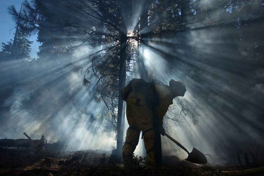 """Mopping up"": Los Angeles County  structure firefighter Jeremy Jones puts dirt on a hotspot. - MARK THIESSEN, NATIONAL GEOGRAPHIC CREATIVE"