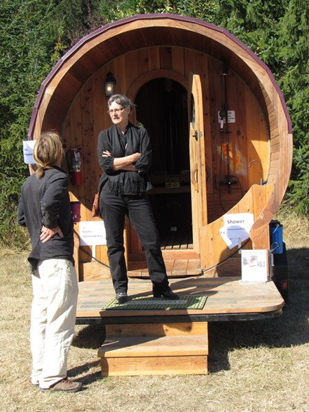 Janelle Egger stands on the porch of a tiny house with its own shower and toilet. - LINDA STANSBERRY