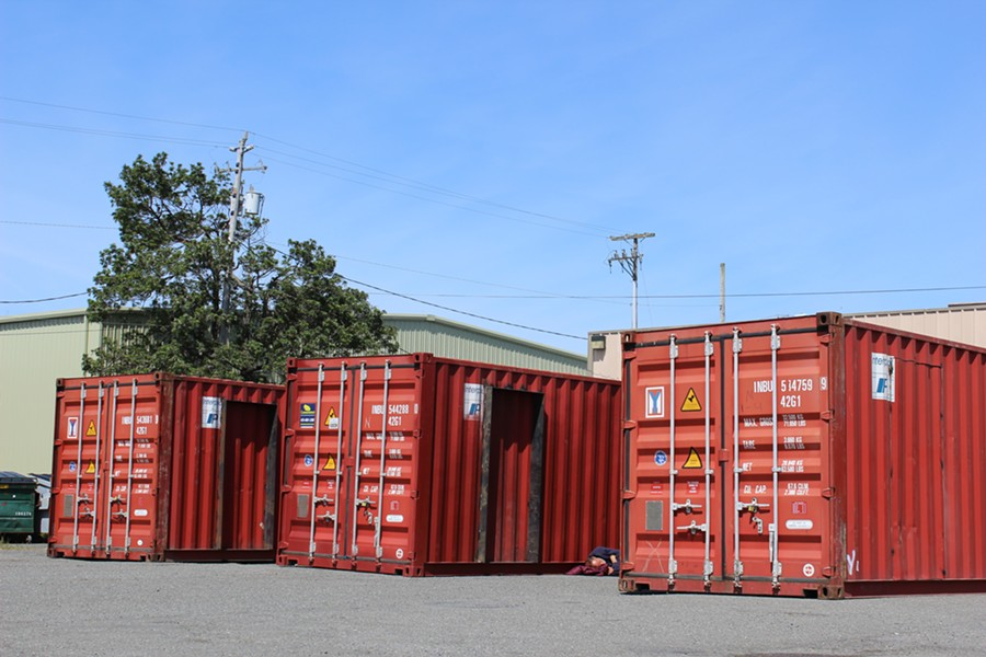 Shipping containers sit in the lot at the corner of Third and Commercial Streets, with renovations having already begun. - THADEUS GREENSON