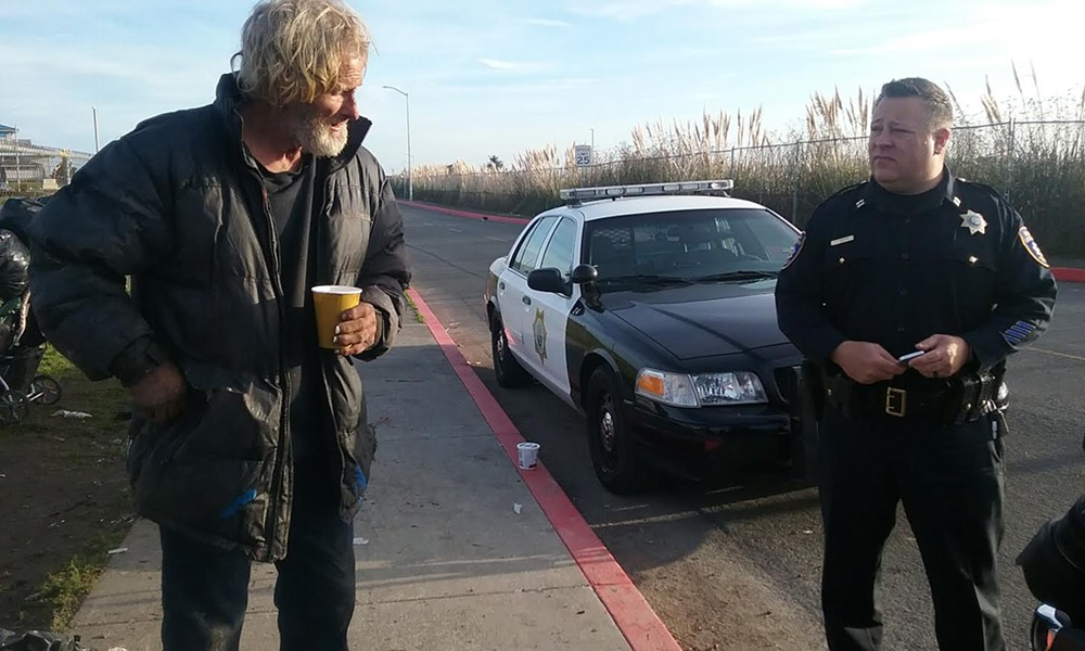 Captain Steve Watson talks to a homeless man vacating the sleeping area this morning. - LINDA STANSBERRY
