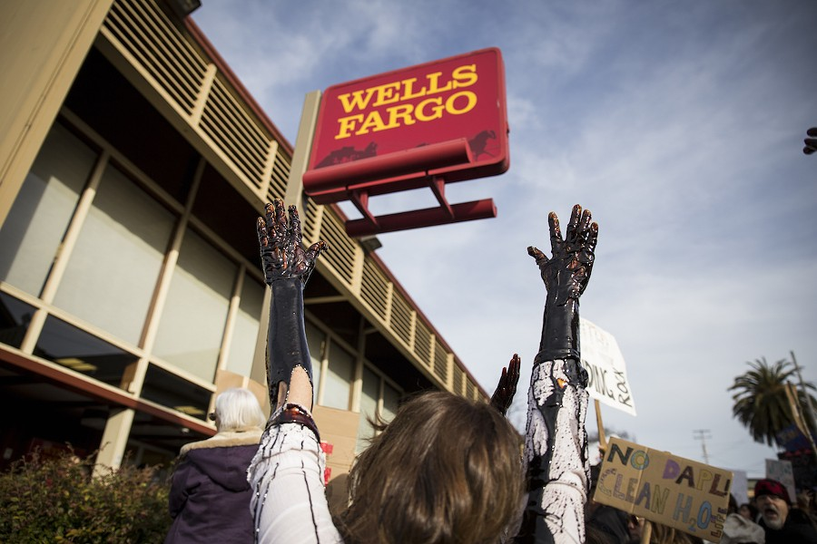 Four protesters brought a large white bucket filled with molasses, which mimicked the look of oil as they let it drip down their arms in protest of Wells Fargo. - SAM ARMANINO
