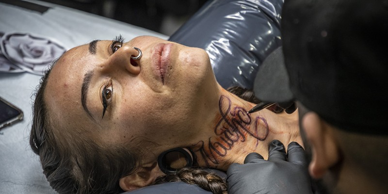 "Tattoo artist David Chavera, of Local Boy Tattoo in San Antonio, Texas, preps a ""Much Love"" design in Spanish on the neck of Roxanne Reche, of Willow Creek."