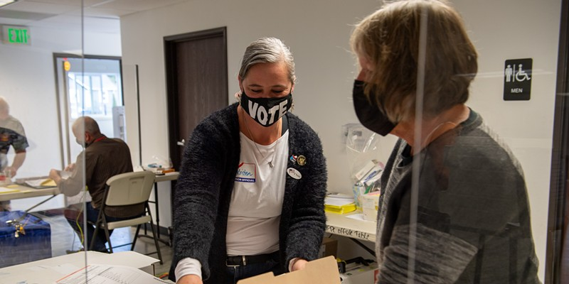 Poll worker Kristen Porter, left, places a ballot in a folder held by Julie Fulkerson at the Eureka Pentecostal Church on Hoover Street. Porter has worked several elections while Fulkerson was working her first at the polls.