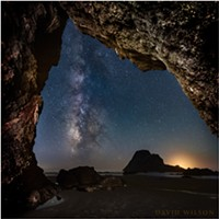 The Milky Way rises from the horizon near the glow of the setting crescent moon outside of this hidden Houda Beach cave. Camel Rock's silhouette is large on the horizon beside the glow of the setting crescent moon. Humboldt County, California. September 13, 2018.