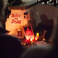 A Justice for Josiah sign and posters of Lawson illuminated by candlelight at the vigil.