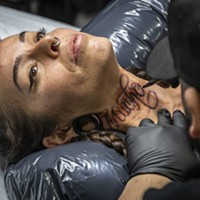 """Tattoo artist David Chavera, of Local Boy Tattoo in San Antonio, Texas, preps a """"Much Love"""" design in Spanish on the neck of Roxanne Reche, of Willow Creek."""