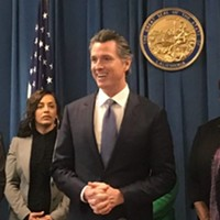 Gov. Gavin Newsom, flanked by authors Sen. Connie Leyva and Assemblyman Patrick O'Donnell, prepares to sign a charter school transparency bill earlier this year.