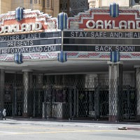 A woman pushes a cart past the shuttered Fox Theater in downtown Oakland on March 25, 2020.