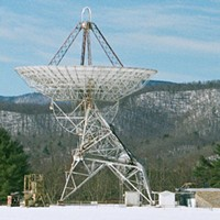"The 85-foot Green Bank WV radio telescope used by Frank Drake in 1960 to monitor two relatively nearby stars for signs of life by ""listening"" to the wavelength emitted naturally by interstellar hydrogen."
