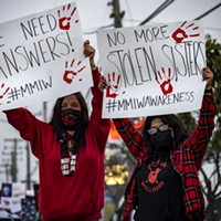 "Yvonne Guido (left) and Wakara Scott (right) stand holding signs reading ""We need answers!"" and ""No more stolen sisters,"" respectively at the Missing and Murdered Indigenous Peoples rally at the federal building in Fortuna."