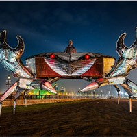 A 14-foot tall, 24-foot wide metal crab kinetic sculpture by Daniel McCauley and Al Hoffman rests down at the Eureka Waterfront. McCauley is in the turret, wearing a welded metal mask he also made. The light-colored tubing outlining the pincers is neon flexible tubing that is brilliant when lit, but it was not powered for this shot. Dec. 2, 2020, Humboldt County, California.