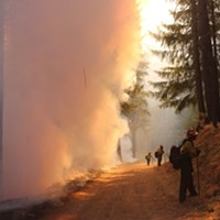 Firefighters hold the line during a burning operation on the northwest flank of the August Complex North Zone on Sept. 26, 2020. These firefighters are positioned with the job of looking into the unburned forest while watching for spot fires created by embers floating across the control line in the wind. This way they can quickly respond to these spotfires to contain them.