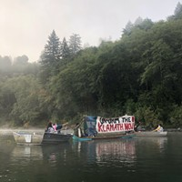 A floating blockade stretches across the Klamath River waiting to stop boats carrying Yurok and Karuk tribal officials and Berkshire Hathaway executives upriver on Aug. 28, 2020.