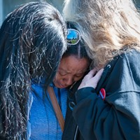 Charmaine Lawson is hugged by supporters at a 2019 vigil for her son, David Josiah Lawson.
