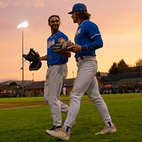 Outfielders Tyler Ganus (left) and Josh Lauck (right) head out to take the field as the sun begins to set over Arcata Ball Park on July 27.