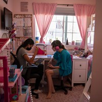 """Ellie sits in her room with a behavioral therapist during class time in Monrovia, on Sept. 15, 2021. """"There is no way to go back with 37 kids in a classroom,"""" Julie Fitzgibbons, the mother of triplets, said. """"With masks and not being able to communicate very well, and autism, there is just no way we can go back like normal."""""""
