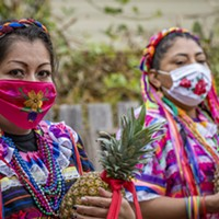 Dancers from Centro del Pueblo carrying pineapples used in their performance awaited the start of their dance in the garden at the Jardin Santuario.