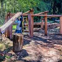 Construction crew members Senior Park Aide Jake Reed (left) and Yurok Trail Crew members Napooi Shorty and Michael Wolf (partially hidden) lift the first of the new roof planks onto the framework of the new women's Dressing House in Sue-meg Village.