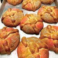 "Cooling pan de muerto loaves crossed with ""bones."""