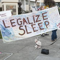 "Carla Ritter, left, and Carlene ""CC"" Schultz, both of Fieldbrook, hold a banner supporting the decriminalization of sleeping in public. Schultz says she spent a year houseless in Humboldt County before getting a home. She said she had also been a ""street mom"" for eight to 10 years helping kids on the street and others when she had an RV."