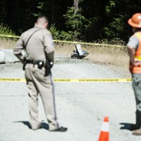 What appears to be part of a plane engine and propeller lie on an access road near the crash site.