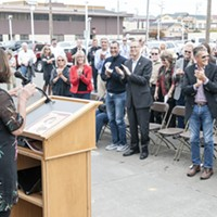 Betty Chinn gets a standing ovation at the grand opening of her new family shelter on Friday.