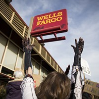 Four protesters brought a large white bucket filled with molasses, which mimicked the look of oil as they let it drip down their arms in protest of Wells Fargo.