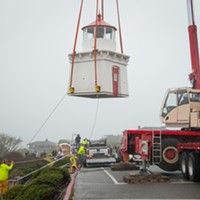 Two workers use ropes to align the lighthouse as it is moved to a trailer.