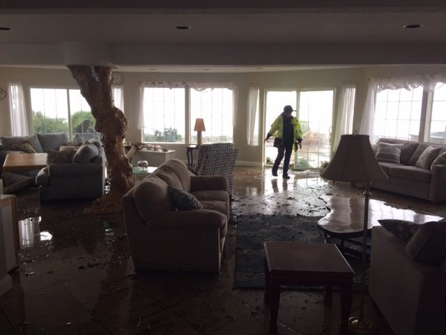 A member of Shelter Cove Fire inspects the damage including water on the floor of this custom-built home. - CHERYL ANTONY OF SHELTER COVE FIRE