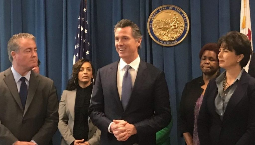 Gov. Gavin Newsom, flanked by authors Sen. Connie Leyva and Assemblyman Patrick O'Donnell, prepares to sign a charter school transparency bill earlier this year. - PHOTO FOR CALMATTERS BY RICARDO CANO