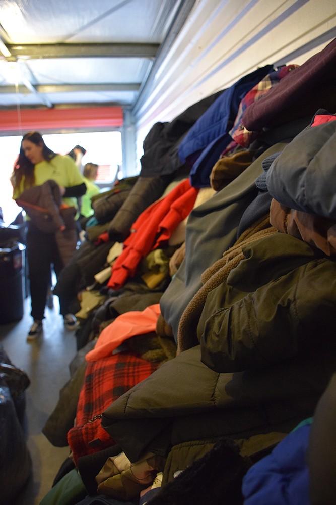 Volunteers sort hundreds of donated coats. - PHOTO BY THADEUS GREENSON