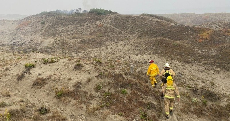 Firefighters hiking to the incident while smoke rises over a dune. - PHOTO BY TED MCNAMEE