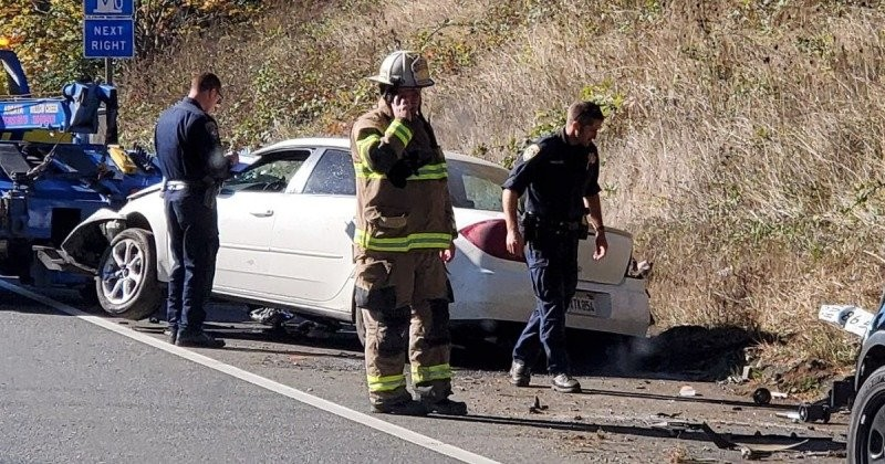 A tow truck hooks up to the crashed vehicle while emergency personnel investigate the scene. [Photo by Jessica Sutton]