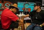 "Nahaan (left), of Seattle, was one of the few tattoo artists present at the event who specialized only in ""native ink."" He focuses on the design style of Northwest Pacific Coast practices, designs and customs of ceremonial tattooing."