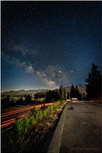 Streaks of humanity pierce the night even as the half moon bathes the forested landscape in its soothing luminance. At the far end a fellow traveler of the night sheltered in their car's bubble of light. Vista Point, Humboldt County, California.