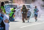"""""""Bigfoot"""" (James Kleinhans, of Klamath) and other participants in the Ney-Puey Color Run passed another color checkpoint dose of colored powder."""